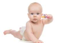 6 month child girl lying happy holding baby nipple soother in hand on a white background